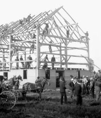 People working together, like this barn raising, is more effective than praying about it